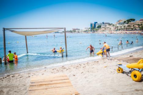 Ocho voluntarios atienden a bañistas con movilidad reducida en la playa adaptada de Aguadulce