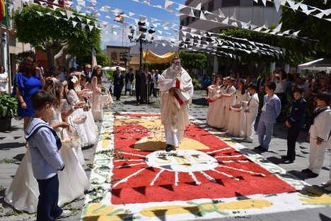 Niños de Primera Comunión acompañan al Corpus alfombrando con pétalos las calles de Gádor
